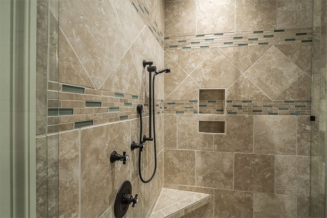 A shower with beige patterned tiles