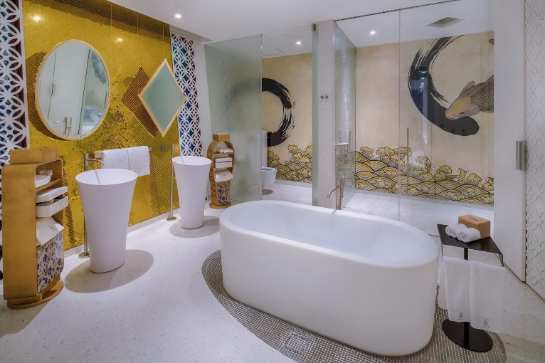 Colourful bathroom with very intricate decorative features and separate bath and shower rooms.