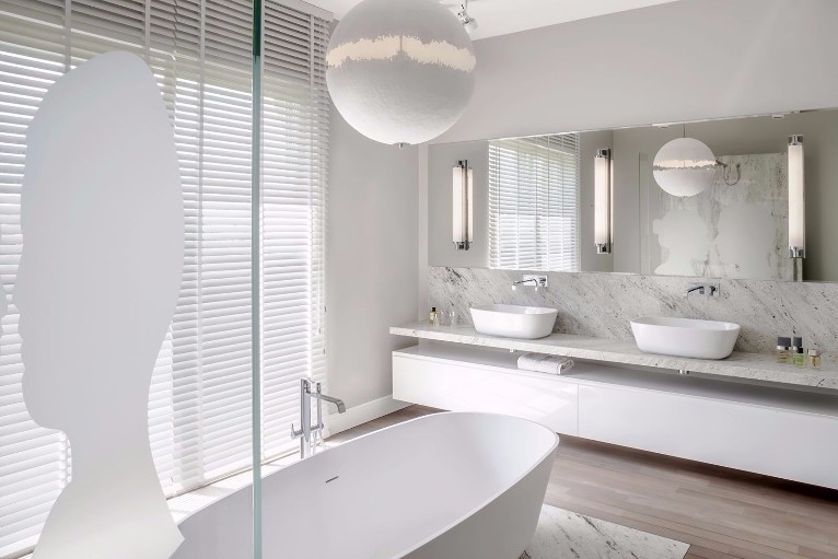 White minimalist bathroom featuring double sink and large freestanding bath tub.