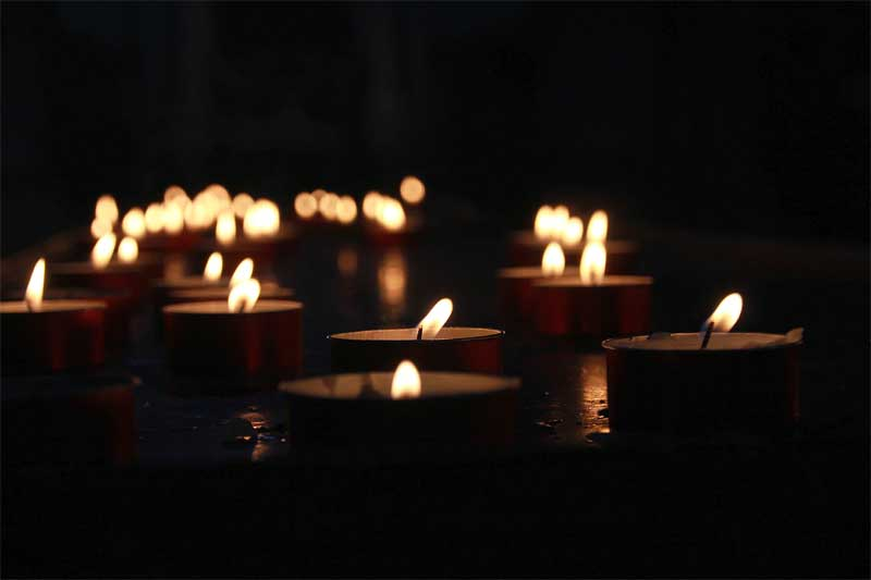 Some lighted tealight candles floating on water