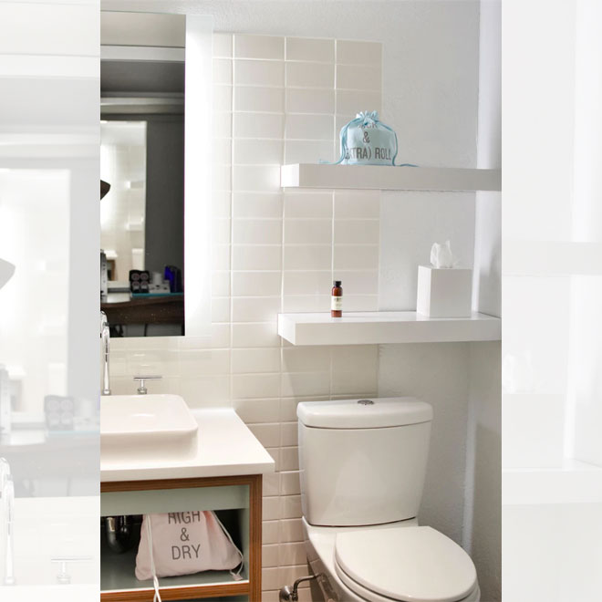 A small white bathroom with convenient shelving installed above the toilet.