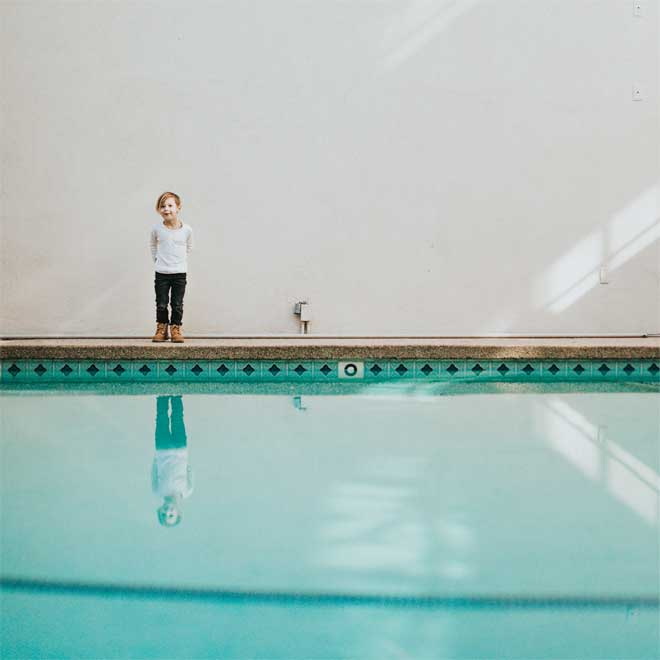 A child stood by an outdoor swimming pool