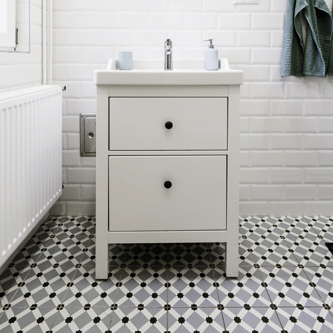 A white bathroom with patterned grey floor tiles