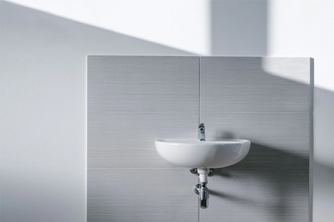 A white bathroom sink back by light grey wall tiles.
