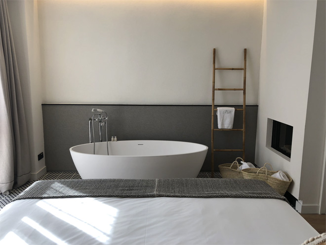 A bedroom with a freestanding bath. The wall behind is grey at the bottom and white on top
