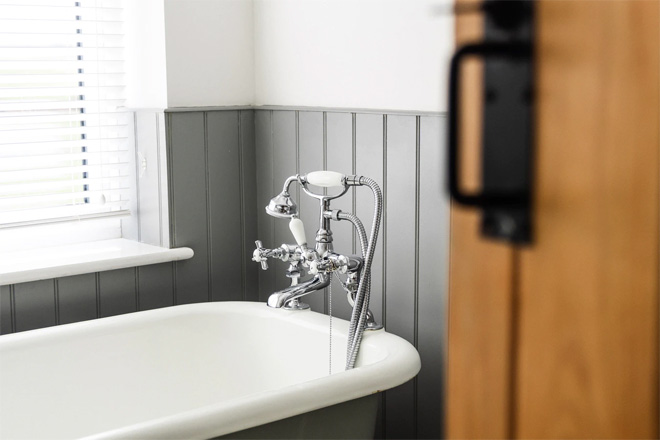 A white and grey freestanding bathtub with grey wooden panelling.