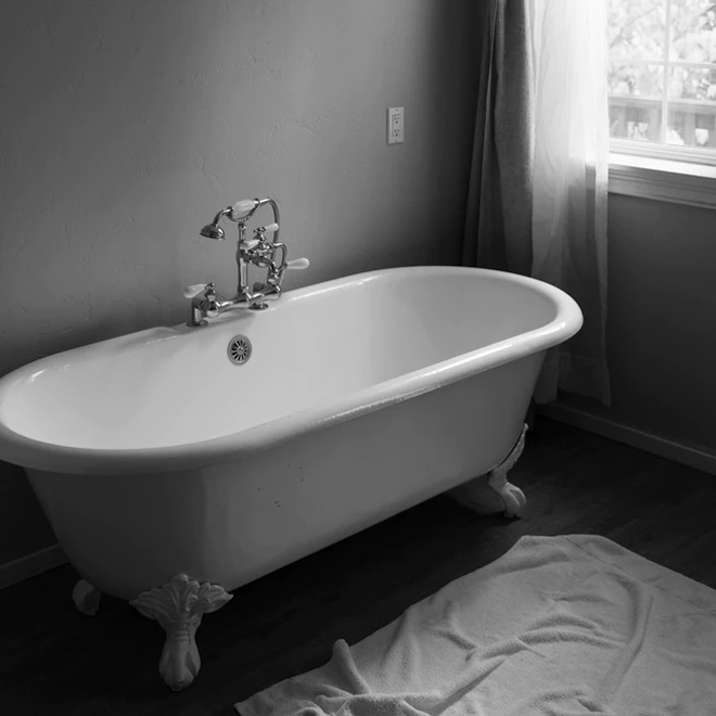 A white freestanding bath with a grey floor and painted grey walls