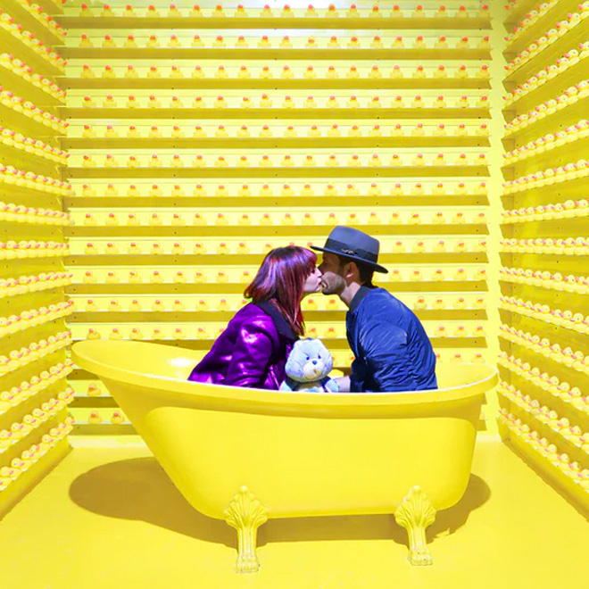 A fully dressed couple sat in a yellow bathtub in a yellow room