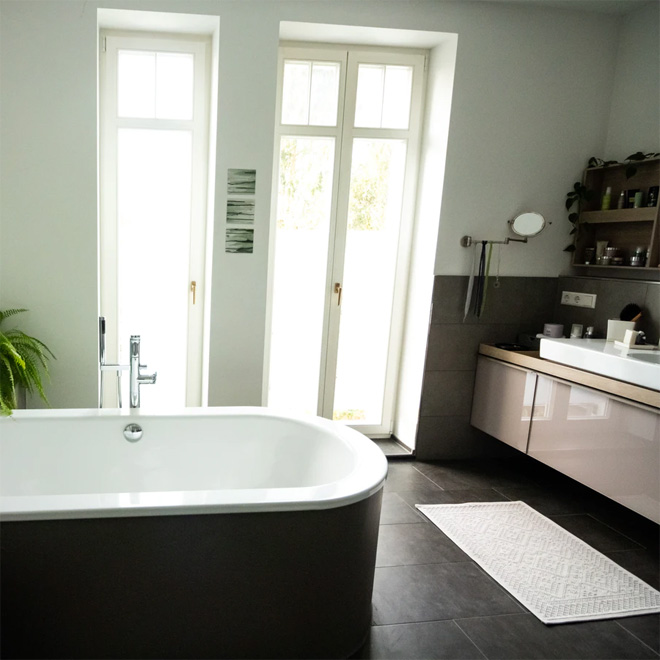 A modern bathroom with black tiled floor and freestanding bath