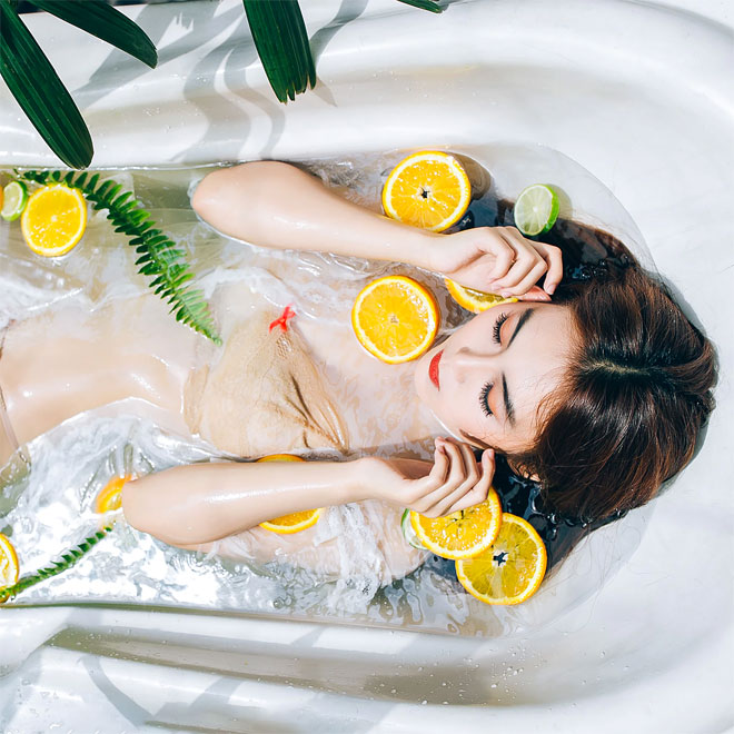 A girl in a bath with orange slices