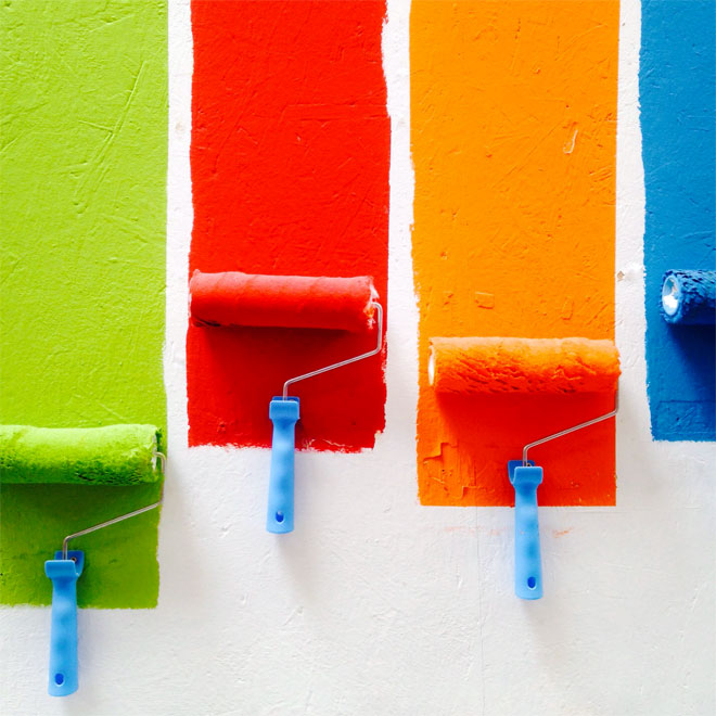 Some paint rollers applying different colours to a wall