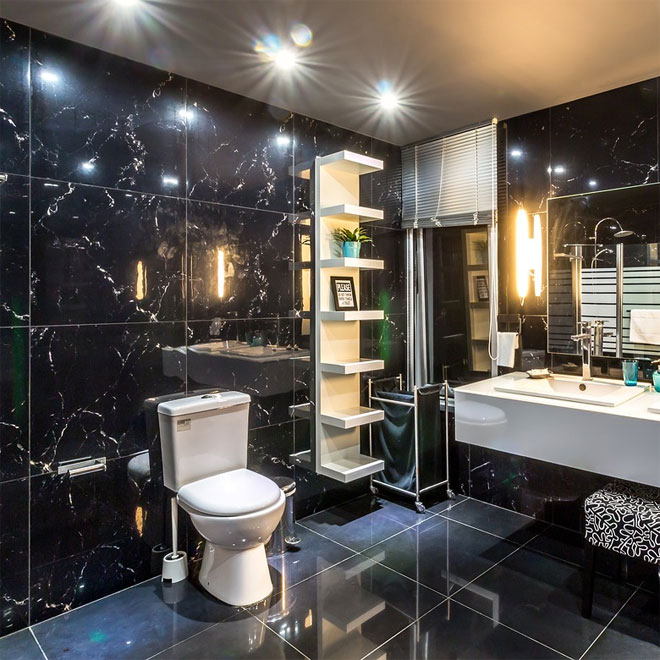 A Bathroom with shiny black tiles