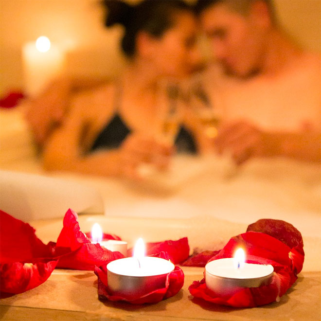 Two people enjoying a candlelit bath with champagne