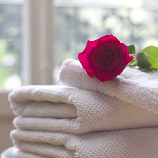 A red rose on top of some white towels in a nicebathroom