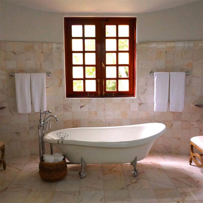 A freestanding bath tube under a window