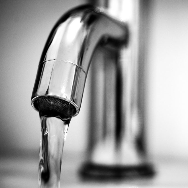 A chrome mixer tap with running water