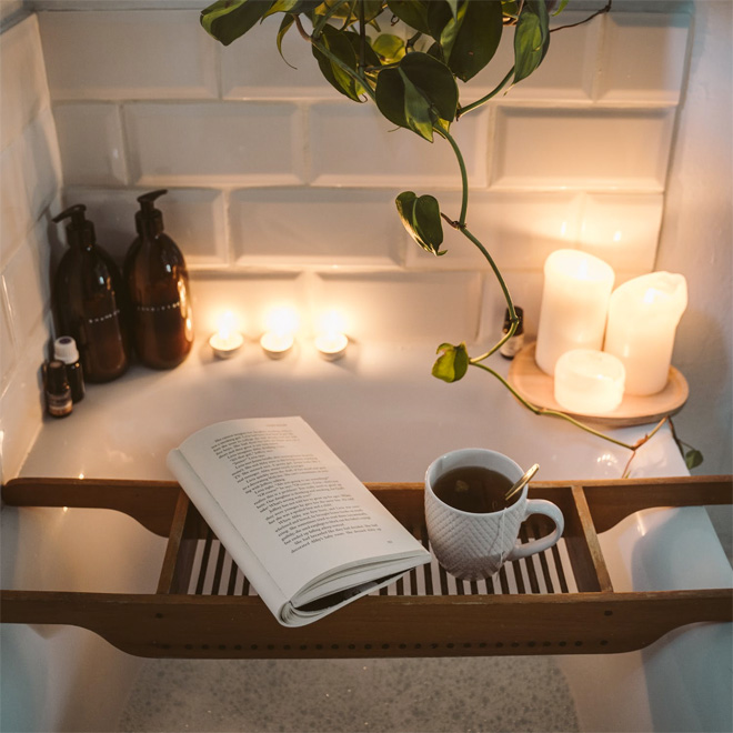A small white bath with candles, cup of coffee and a book