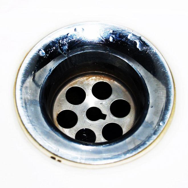 A dirty plug hole in a bathroom