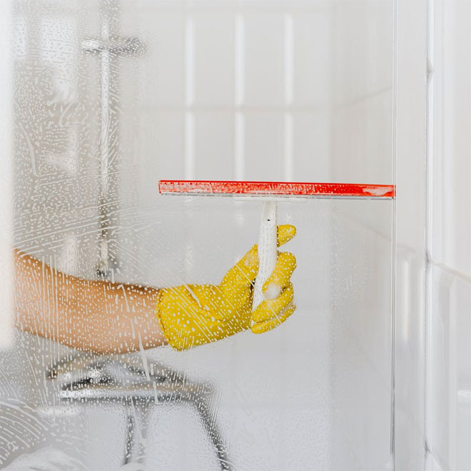 Someone cleaning a shower screen with a squeegee