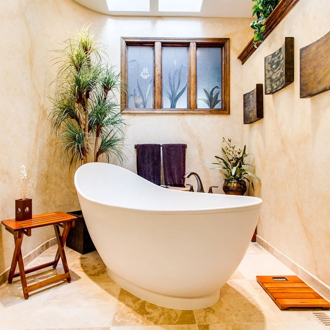 A beautiful freestanding bath under a window surrounded by plants