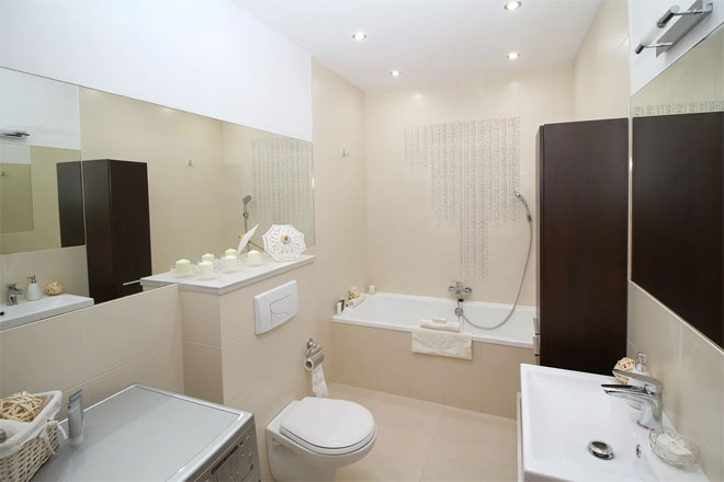 A cream and white windowless bathroom with bath, toilet and basin.